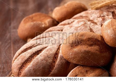 Assortement of fresh bread on the wooden table. Brown background. Brown bread. Close-up. Flour. Delicious food. Fresh baking. Tasty and appetizing.