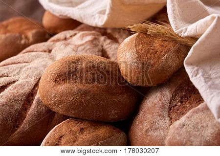 Assortement of fresh bread with white cloth and ears of wheat. Background of the brown bread. lose-up. Flour. Delicious food. Fresh baking. Tasty and appetizing.