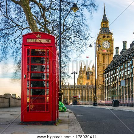 London England - The iconic british old red telephone box with the Big Ben at background in the center of London