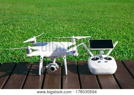 drone quad copter with high resolution digital camera and its remote control pad with smartphone on grass