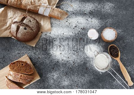 Cooking of homemade bread black round bread and baguette lie on parchment paper on a dark background with flour sliced bread on a cutting board paper and salt. Space for text daylight.