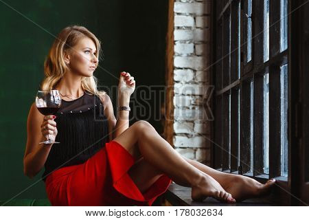 Beautiful Slim woman in a black blouse and Red Skirt with a Glass in Hand. Portrait of Luxury Female in Loft Interior near The Window.