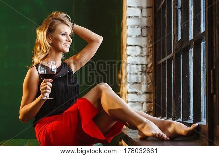 Beautiful Slim woman in a black blouse and Red Skirt with a Glass in Hand. Luxury Blue-eyed Blonde Holding Her Perfect Hair Near The Window in Loft Interior.
