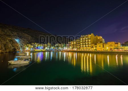 Xlendi Gozo - Beautiful aerial view over Xlendi Bay by night with restaurants boats and busy night life on the Island of Gozo
