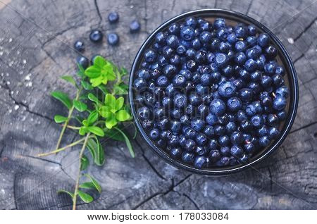 ripe bilberry in a bowl on a wooden background