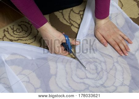 The Woman Cuts The Fabric With Scissors For Sewing Curtains On The Window. The Fabric Lies On The Fl