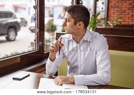 Young manager working writes in a notebook outdoors. Freelancer works in a cafe.
