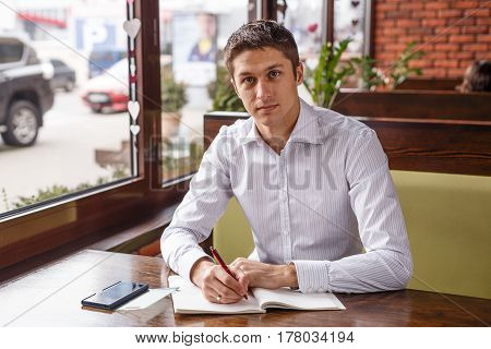 Portrait of an handsome business man working in cafe. Young manager writes in a notebook outdoors.