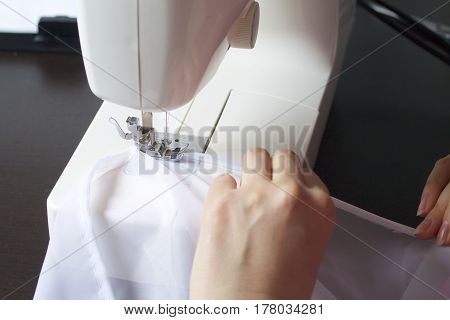 A Woman Works On A Sewing Machine. She Sews The Curtains On The Window.
