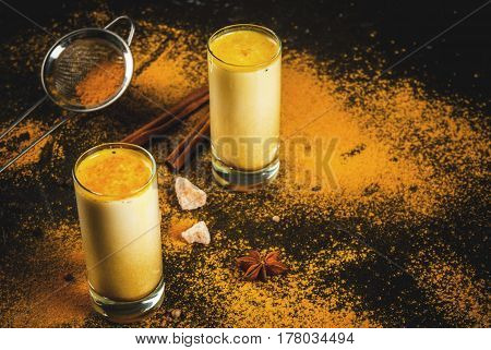 Traditional Indian drink turmeric milk is golden milk with cinnamon cloves pepper and turmeric. On a concrete table with spices on the background. In glasses Horizontal toned copy space