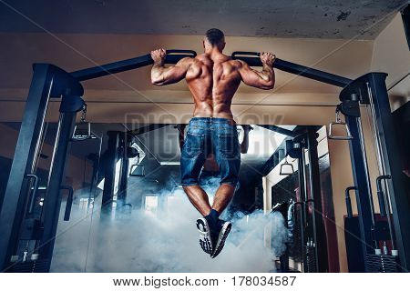 Young athlete exercising on bars in gym