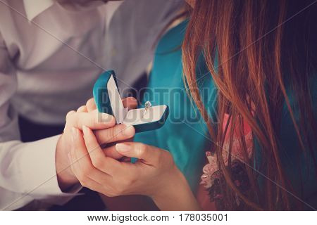 A young man makes an offer to his girlfriend handing her an engagement ring