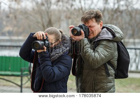 Man and girl photographed outdoors on cloudy spring day.