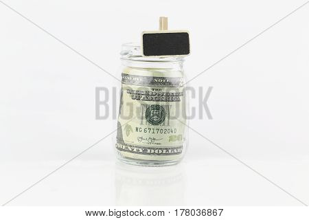 A jar filled with US dollar bills on a table with chalk board
