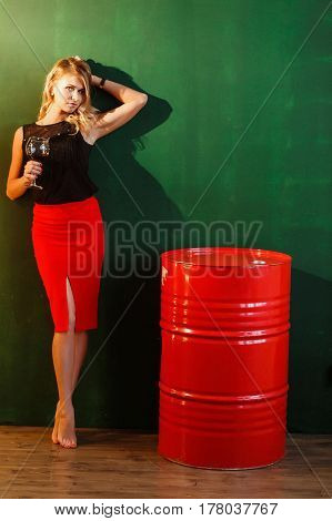Woman in Red Skirt Stands Near the Barrels of oil. Sexy Attractive Blonde Holds Glass of Wine and Looks to Camera.