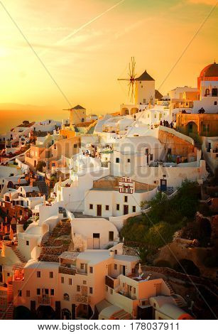 famouse pink and orange sunset of Oia with windmill, Santorini, retro toned