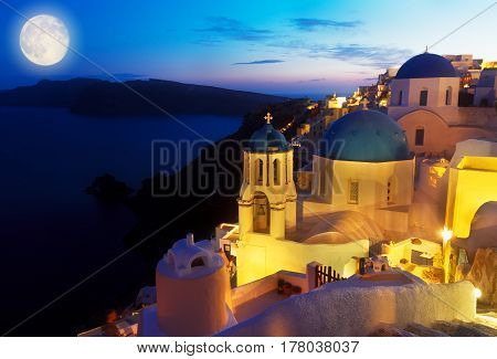 Oia village with blue church domes at night at night, Santorini, Greece, toned