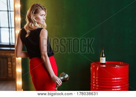 Woman in Red Skirt Stands Near the Barrels of oil. Sexy Attractive Blonde Holds Glass of Wine and Looks to Window.