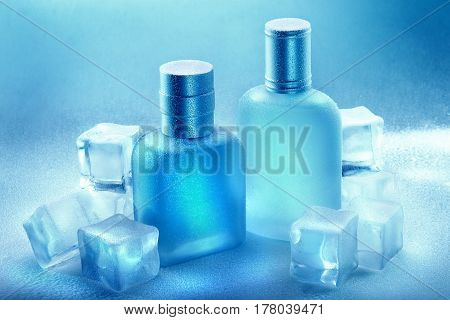 Men's Perfume in blue bottles with water droplets and pieces of ice around. Male beauty concept