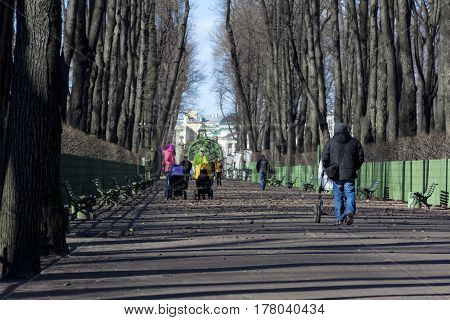 people men women girls with baby strollers walking along the path in the Park spring Sunny day Petersbugr Russia summer garden