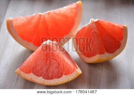 Pink grapefruit slices on a wooden board