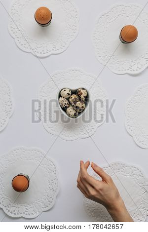Woman Reaching for Quail Eggs in Heart Shaped Dish on White Table