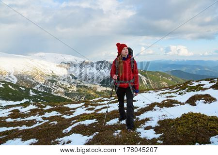 Dreamy blonde girl walking with great sport backpack far away from home watching the beautiful mountain landscapes and picturesque sky.