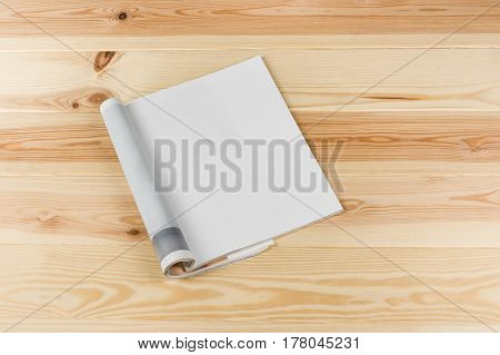 Mock-up magazine or catalog on natural wooden table. Blank page or notepad on wood background. Blank page or notepad for mockups or simulations.