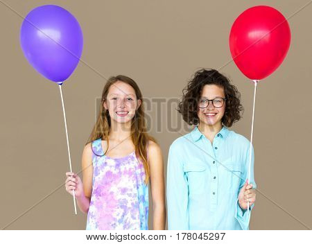 Two girl is holding a color balloon