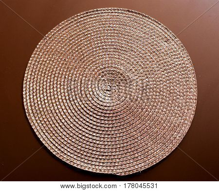 Round Woven Place Mat On A Dark Wood Background