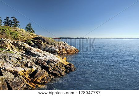 Rocky beach in the  Strait of Georgia British Columbia, a coastline and a forest.