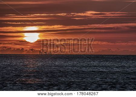 Red dawn at sea. Beautiful sunrise as low cloud causes a futuristic red sky. Natural colors lightly saturated.