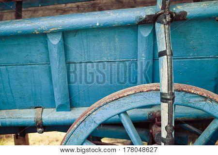 Old Retro Vintage Wooden Trailer With Blue Wheel Close Up, Detail. Countryside View On The Farm