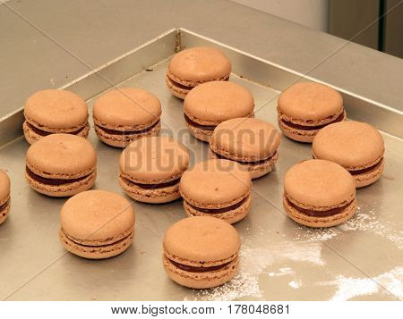 Chocolate macaroons background on industrial kitchen.