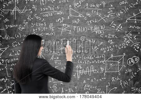 Rear view of a black haired woman writing formulas on a blackboard in front of her. Concept of exact sciences.