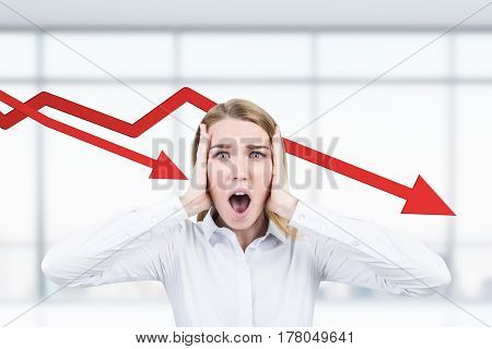 Portrait of a stressed out businesswoman crying in dispair while standing in her office with two falling graphs in the background.