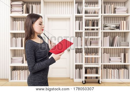 Side view of a woman reading a red book in a white library. Concept of reading and working with information.