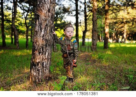 Child boy soldier in military uniform, with a gun on a nature background. Victory Day, May 9, memory, February 23