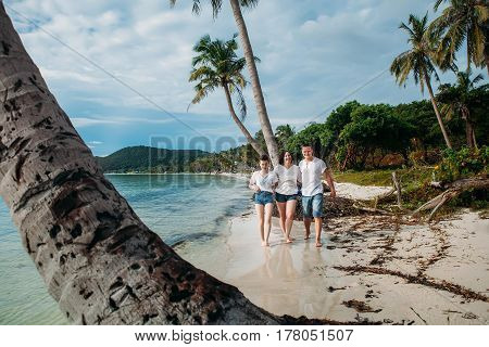 Family stand on tropical palm beach Vietnam Phu Quoc
