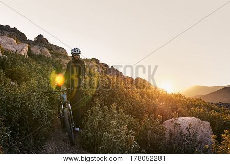 The cyclist on the mountain at sunset