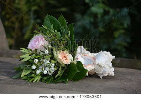 Roses - Bouquet lies with a mussel on wood