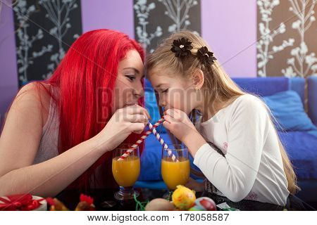 Mother and daughter drinking juice and having fun