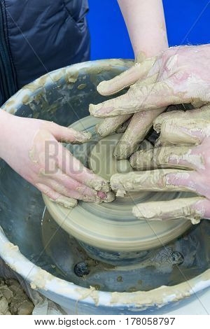 The Master Teaches The Child, A Student Of Pottery. Helps To Make Out Of Clay On A Potter's Wheel A