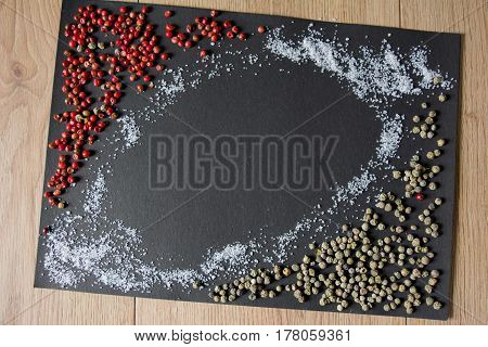 Sea salt and colorful peppercorns on a black background. Red and Green peppercorn.