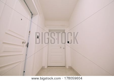 Corridor in a building. White staircase. Interior hallway with doors to the neighbors.