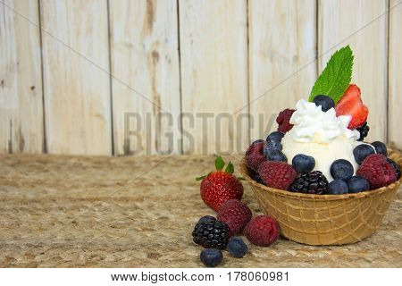 fresh berries and ice cream in waffle bowl with whipped cream and mint leaf garnish