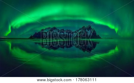 Aurora reflections on Stokksnes black beach with Vestrahorn mountains in center Iceland