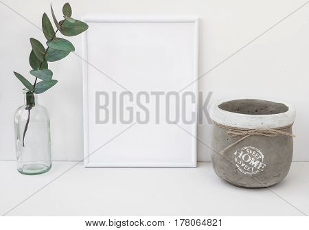 White frame mockup eucalyptus branch in glass bottle cement bowl styled minimalist clean image for product marketing social media blogging