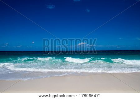 A peaceful tropical beach view of the ocean with a clean blue sky. New Providence, Nassau, Bahamas.
