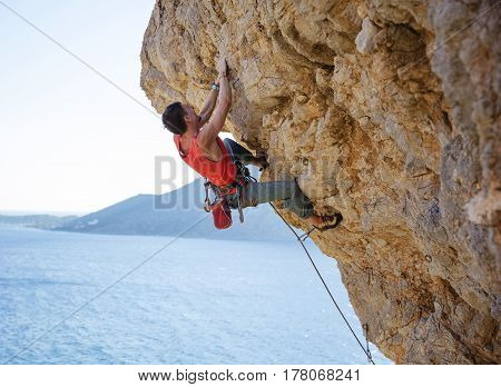 Young man lead climbing on overhanging cliff over water